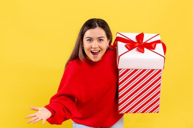 Vue de face de la jeune femme tenant un cadeau de noël en boîte sur mur jaune