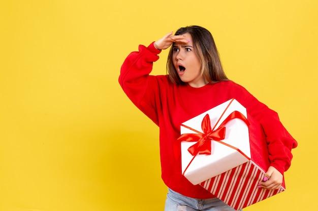 Vue de face jeune femme tenant un cadeau de noël étonnamment à la distance sur fond jaune
