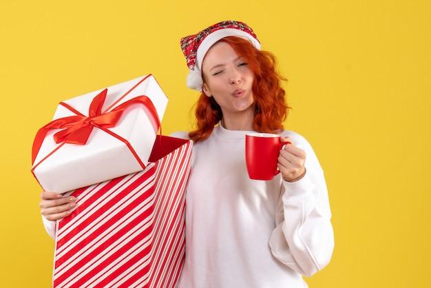 Vue de face de la jeune femme tenant un cadeau de noël et une tasse de thé sur un mur jaune