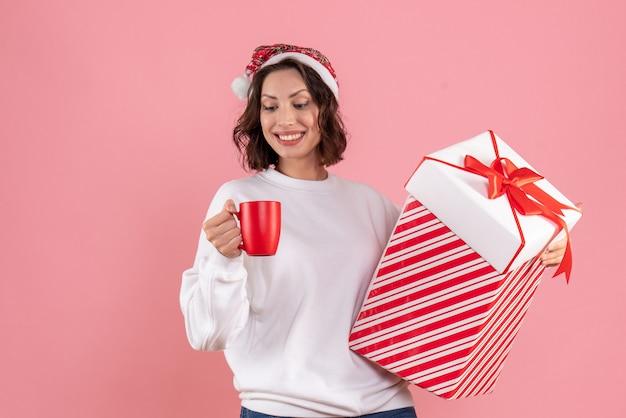Vue de face de la jeune femme tenant un cadeau de noël et une tasse de thé sur le mur rose