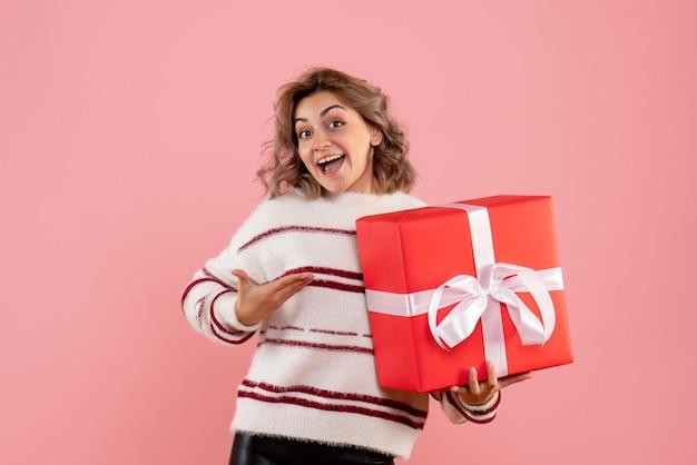 Vue de face jeune femme tenant cadeau de noël
