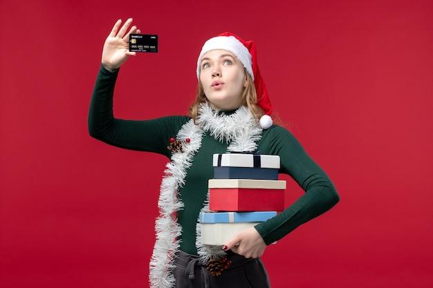 Vue de face jeune femme tenant des cadeaux et une carte bancaire sur fond rouge