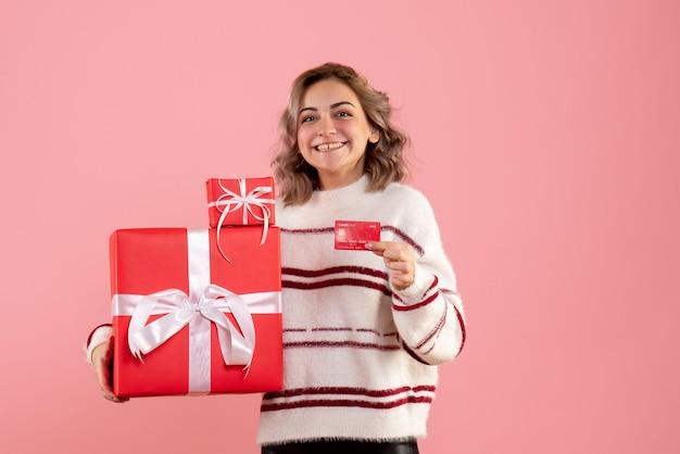 Vue de face jeune femme tenant des cadeaux de noël et carte bancaire