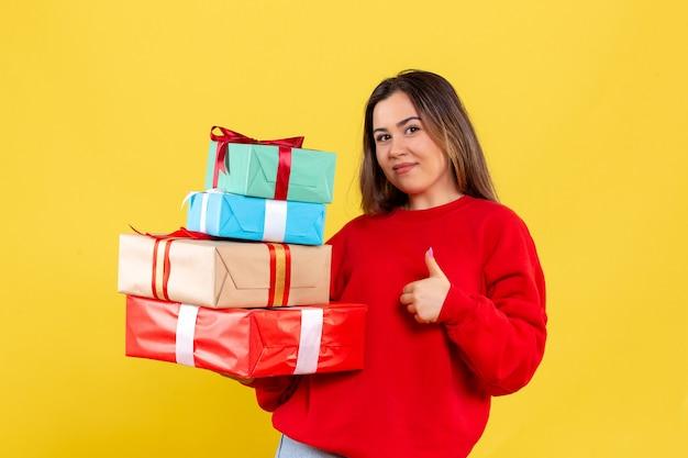 Vue de face jeune femme tenant des cadeaux de noël sur fond jaune