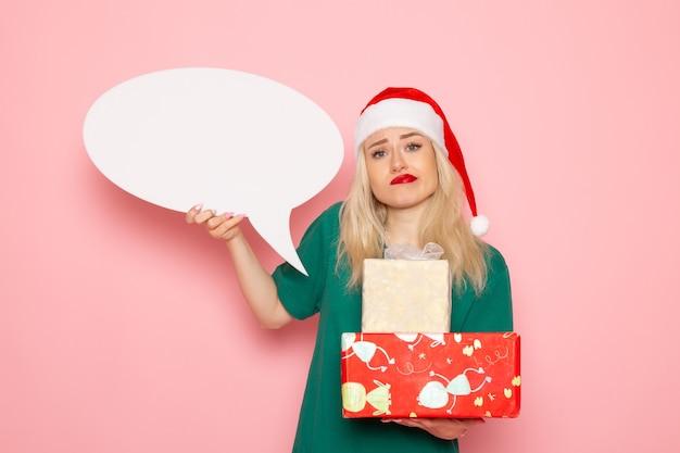 Vue de face jeune femme tenant des cadeaux de noël et panneau blanc sur mur rose femme cadeau neige couleur photo vacances de nouvel an