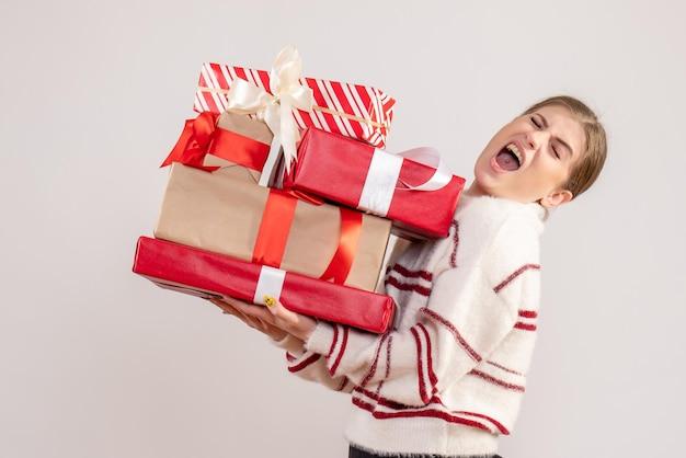 Vue de face jeune femme tenant des cadeaux de noël