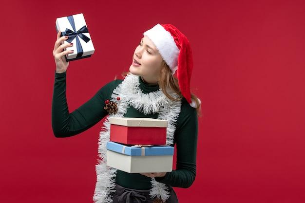 Vue de face jeune femme tenant des cadeaux de nouvel an sur un bureau rouge