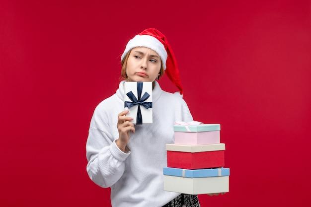 Vue de face jeune femme tenant des cadeaux de nouvel an sur fond rouge