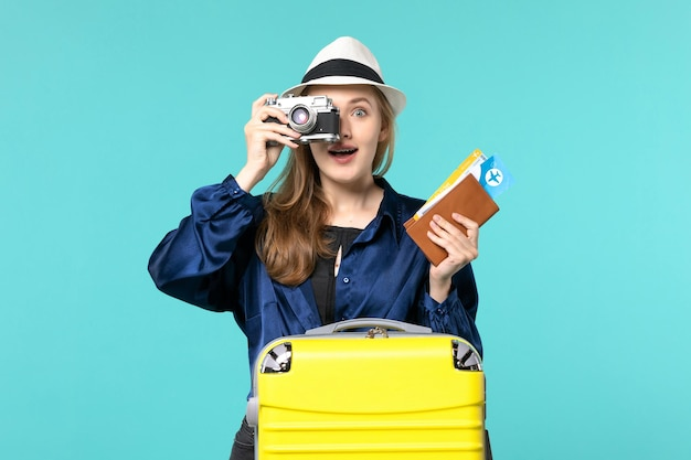 Vue de face jeune femme tenant la caméra et les billets sur fond bleu mer voyage voyage vacances voyage avion