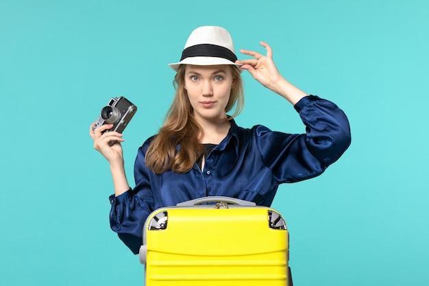 Vue de face jeune femme tenant la caméra et posant sur fond bleu femme voyage mer voyage avion