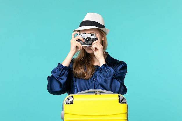 Vue de face jeune femme tenant la caméra et prendre des photos sur le fond bleu femme voyage mer voyage voyage avion
