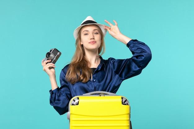 Vue de face jeune femme tenant la caméra et souriant sur fond bleu femme voyage avion de voyage en mer