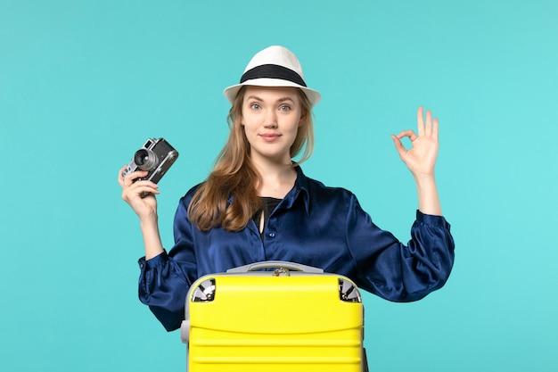 Vue de face jeune femme tenant la caméra et souriant sur le fond bleu femme voyage voyage avion mer