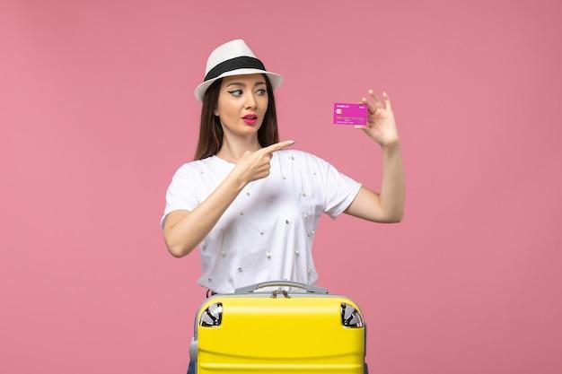 Vue de face jeune femme tenant une carte bancaire sur l'argent de vacances de femme de voyage de bureau rose