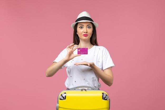 Vue de face jeune femme tenant une carte bancaire sur l'argent de vacances de femme de voyage de mur rose