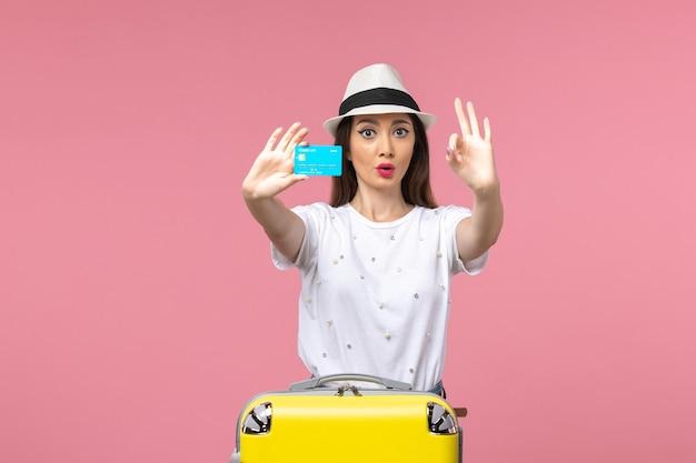 Vue de face jeune femme tenant une carte bancaire bleue sur un mur rose clair voyage voyage été