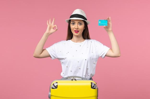 Vue de face jeune femme tenant une carte bancaire bleue sur un voyage de couleur de mur rose clair