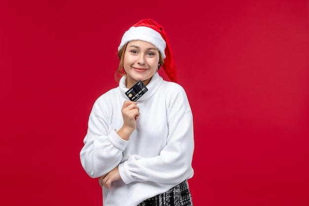 Vue de face jeune femme tenant une carte bancaire sur un bureau rouge