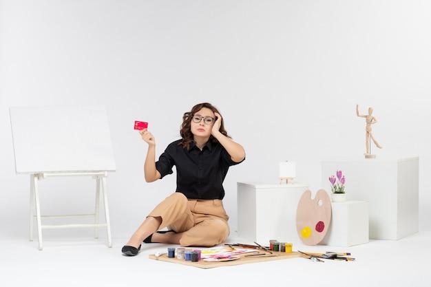 Vue de face jeune femme tenant une carte bancaire sur fond blanc