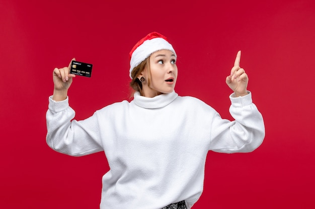 Vue de face jeune femme tenant une carte bancaire sur fond rouge clair