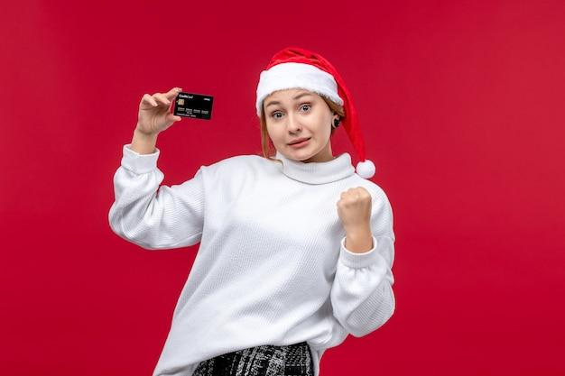 Vue de face jeune femme tenant une carte bancaire sur fond rouge