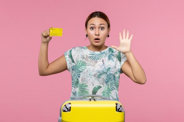 Vue de face d'une jeune femme tenant une carte bancaire jaune sur le mur rose