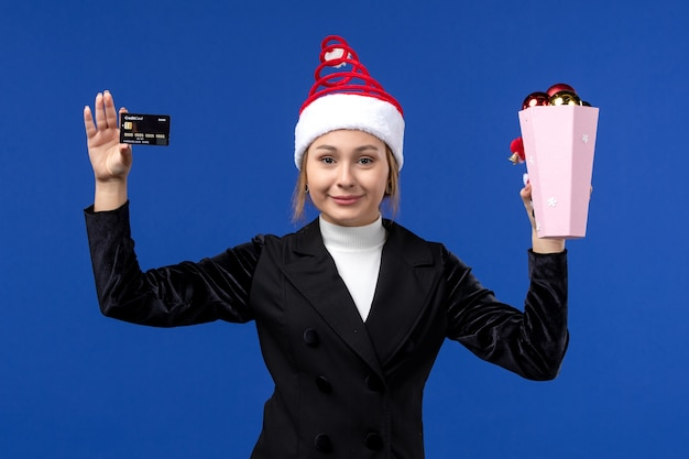 Vue de face jeune femme tenant une carte bancaire sur le mur bleu nouvel an émotions vacances jouet