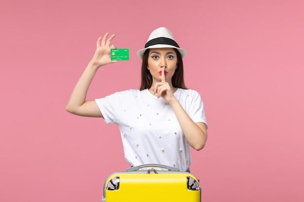 Vue de face jeune femme tenant une carte bancaire sur un mur rose clair femme d'émotion de voyage d'été