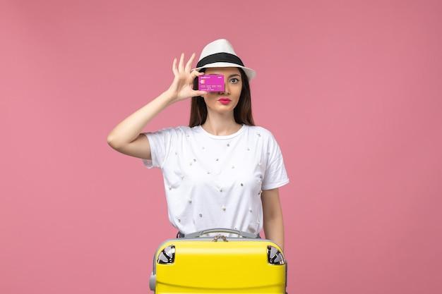 Vue de face jeune femme tenant une carte bancaire sur un mur rose clair voyage couleur argent vacances