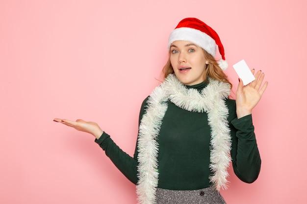Vue de face jeune femme tenant une carte bancaire sur le mur rose couleur émotion modèle vacances noël nouvel an