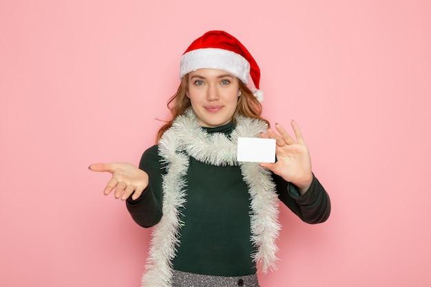 Vue de face jeune femme tenant une carte bancaire sur le mur rose couleur modèle vacances noël nouvel an émotion
