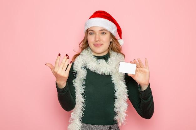 Vue de face jeune femme tenant une carte bancaire sur le mur rose couleur modèle vacances noël nouvel an émotions