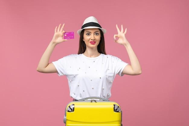 Vue de face jeune femme tenant une carte bancaire sur le mur rose voyage couleur argent vacances