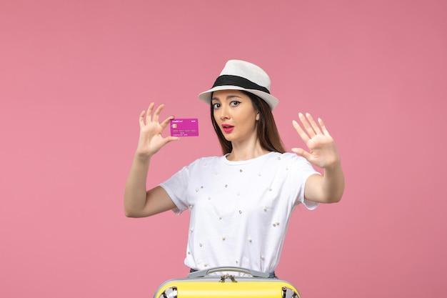 Vue de face jeune femme tenant une carte bancaire sur le mur rose voyage vacances femme argent