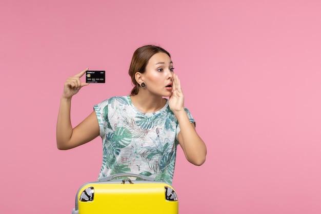 Vue de face d'une jeune femme tenant une carte bancaire noire appelant quelqu'un sur un mur rose