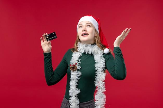 Vue de face jeune femme tenant une carte bancaire noire sur un bureau rouge