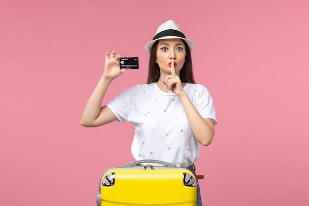 Vue de face jeune femme tenant une carte bancaire noire sur un mur rose voyage couleurs voyage