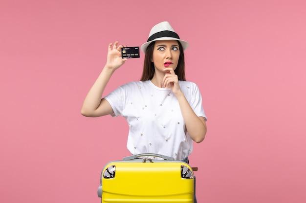 Vue de face jeune femme tenant une carte bancaire noire sur le mur rose voyage voyage été