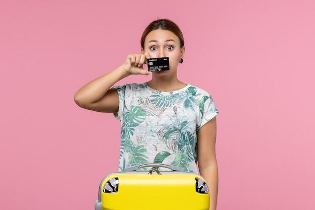 Vue de face d'une jeune femme tenant une carte bancaire noire sur le mur rose