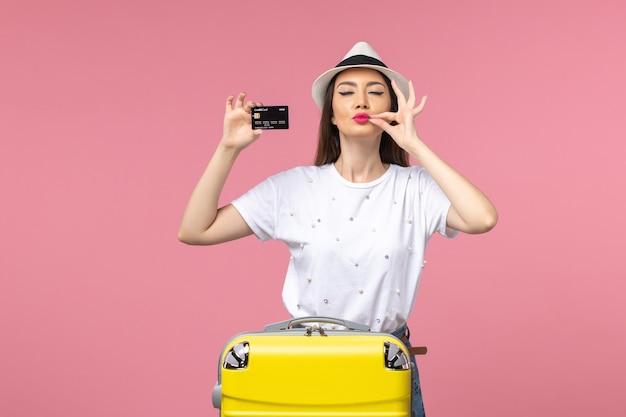 Vue de face jeune femme tenant une carte bancaire noire sur un voyage de couleur de voyage de bureau rose clair
