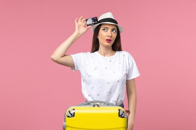 Vue de face jeune femme tenant une carte bancaire noire sur un voyage de couleur de voyage de mur rose