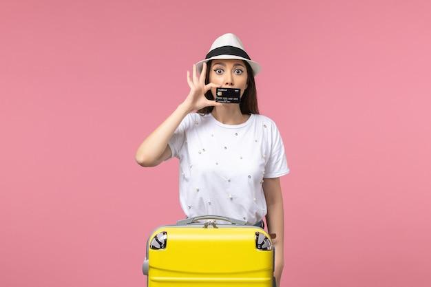 Vue de face jeune femme tenant une carte bancaire noire sur un voyage d'été de voyage de mur rose