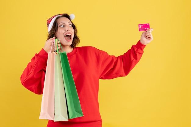 Vue de face jeune femme tenant une carte bancaire et des paquets sur jaune