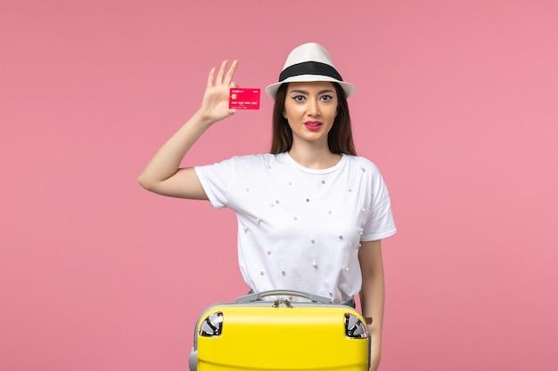 Vue de face jeune femme tenant une carte bancaire rouge sur le voyage d'été de voyage de mur rose