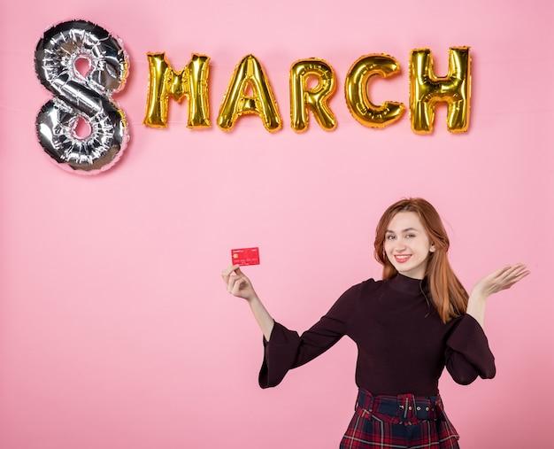 Vue de face jeune femme tenant une carte bancaire sur shopping rose