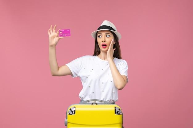 Vue de face jeune femme tenant une carte bancaire sur des vacances de couleur argent voyage bureau rose