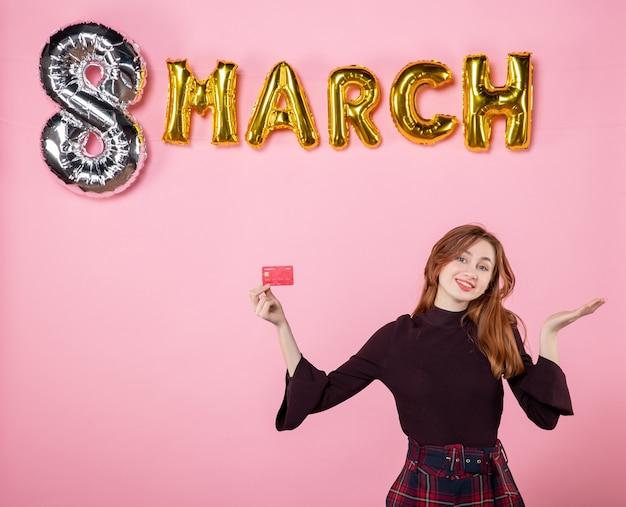 Vue de face jeune femme tenant une carte bancaire en vacances shopping rose