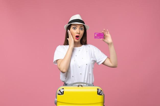 Vue de face jeune femme tenant une carte bancaire sur le voyage d'argent de vacances de femme de mur rose