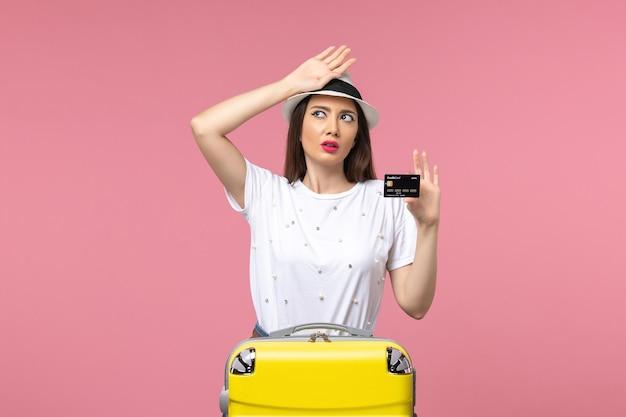 Vue de face jeune femme tenant une carte bancaire sur le voyage d'été de voyage de mur rose