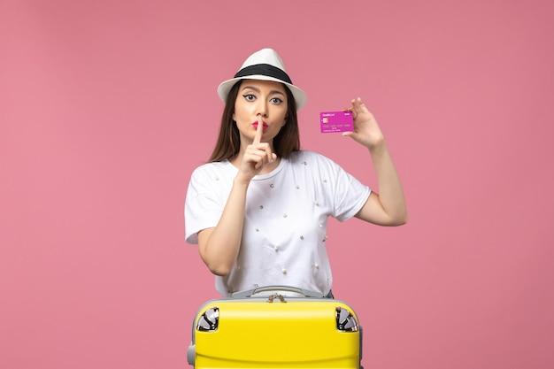 Vue de face jeune femme tenant une carte bancaire sur le voyage de femme d'argent de vacances de bureau rose